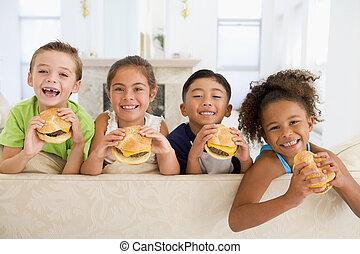 vier, junge kinder, essende, cheeseburger, in, wohnzimmer, lächeln