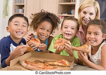 vier, junge kinder, innen, mit, frau essen, pizza, lächeln