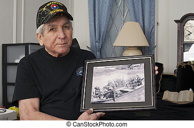Vietnam war veteran holds an old war photo of himself. -...