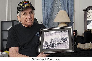 Vietnam war veteran holds an old war photo of himself. -...
