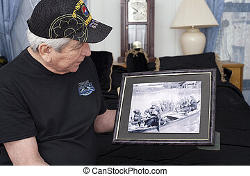 Vietnam war veteran looks at old war photo of himself. -...
