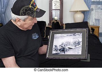 Vietnam war veteran looks at old war photo of himself. -...