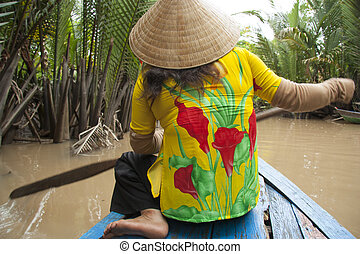 Vietnam woman with a paddle in boat