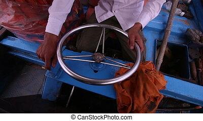 Vietnamese boat captain turns round wheel drifting along...