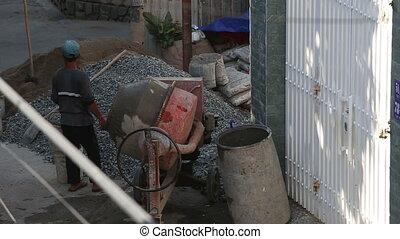vietnamese builder stands near operating concrete mixer