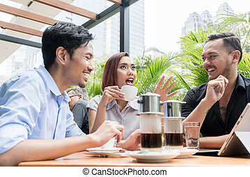 Vietnamese coffee served on the table of three friends outdoors