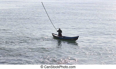 vietnamese fisherman beats water with stick  in small boat