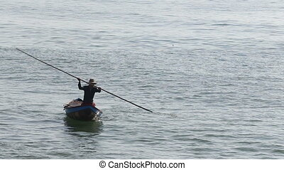vietnamese fisherman drifts in boat using stick - vietnamese...