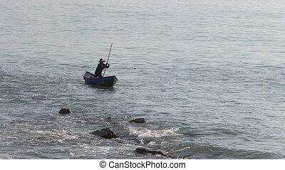 vietnamese fisherman frightens fish in net with stick