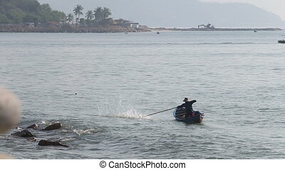 vietnamese fisherman frightens fish in net with stick by...