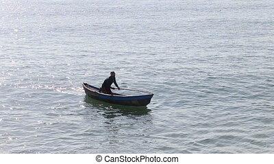 vietnamese fisherman rows in boat using paddle