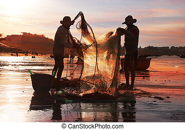 Vietnamese fishermen in the setting sun - Vietnamese...