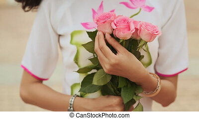 Vietnamese girl holding a bouquet of pink roses