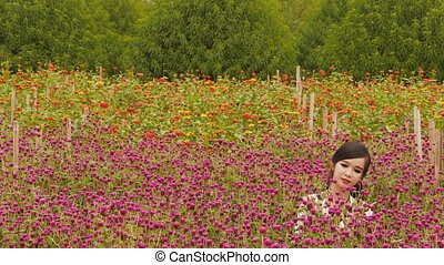 Vietnamese girl sits in the plantation purple flowers.