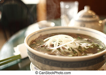 Vietnamese pho noodles with beef at a restaurant.