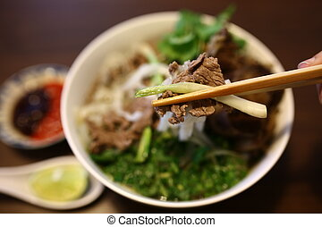 Vietnamese rice noodles are served with beef, lime, hoisin...