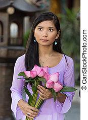 Vietnamese woman holding lotus bunch