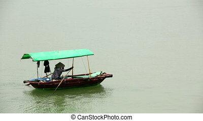 vietnamese woman with traditional dress paddling boat, halong bay, vietnam