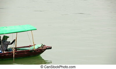 vietnamese woman with traditional dress paddling boat, ...