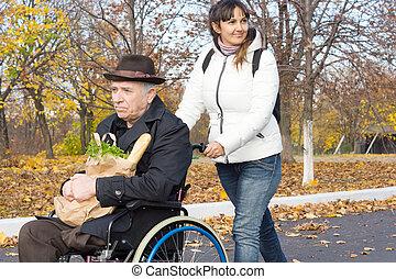 vieux, carer, fauteuil roulant, pousser, homme souriant