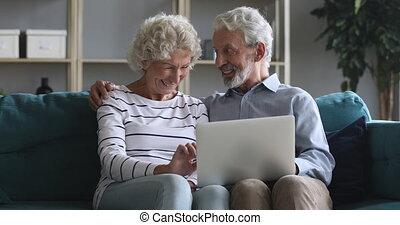 vieux, couple, ordinateur portable, sofa, conversation, rire, asseoir, utilisation, heureux