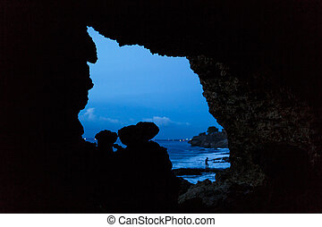 viev from balinesse cave at ocean beach on dark blue sky.