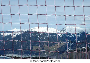 Viev through net hanging nearby slope in Alps nearby ...