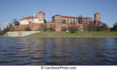 Medieval fortified architectural complex of Wawel Castle and bell tower of Archcathedral Basilica on banks of Vistula river in springtime, Krakow, Poland