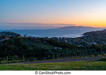 View across Waiheke Island township and sea to the Coromandel peninsula under a golden glow at sunrise.