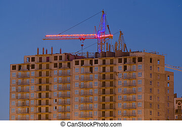 View after sunset on the unfinished house with a crane