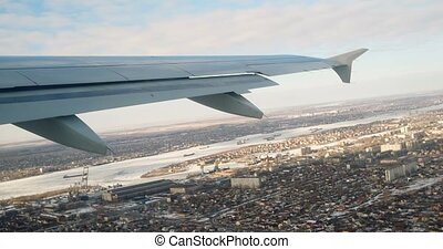 View at aircraft wing from window. Fly over city
