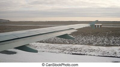 View at aircraft wing from window in winter time, snow on...