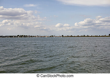View at Durgerdam, seen from a boat on the Markermeer, historic little typical dutch village with wooden houses and a small harbour.