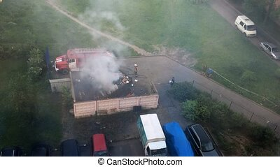 View at firefighters extinguish the fire in dustbin. Camera...