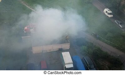 View at firefighters extinguish the fire in yard from...