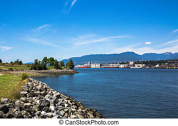 View at  the seaport of North Vancouver from the parkland of Burnaby City. Ships loading at the seaport of North Vancouver against the backdrop of a mountain range and blue sky