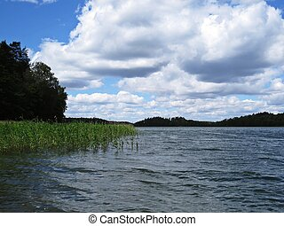 View at Panorama of Tranquil Lake with Trees and Clouds