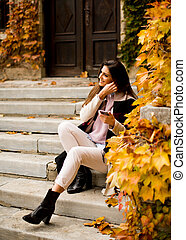 View at pretty young woman outdoor with mobile phone