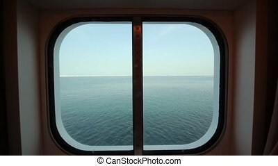 view at sea through sidelight of passenger cabin in cruise...