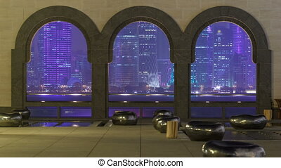 View at the heart of finance world of Doha night timelapse thought the tree arches