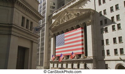 view at new york stock exchange with flags in wall street