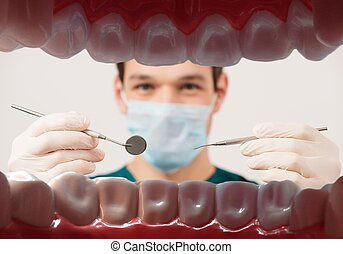 View at young male dentist holding dental tools from patient...