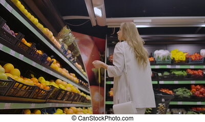 View back girl walking through the supermarket with a basket...