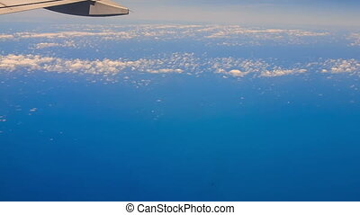 View Clouds Azure Sea under Airliner Wing - panorama of...