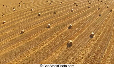 View from a bird's eye view on a field with stacked bales of...
