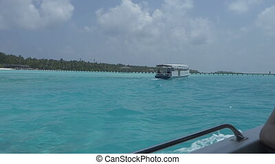 View from a boat on a tropical island with white sand and...