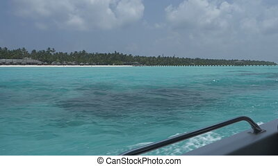 View from a boat on a tropical island with white sand and azure ocean.