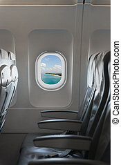 View from a commercial airplane  cabin, showing blue sky, holiday destination and a row of comfortable chairs and arm rests.
