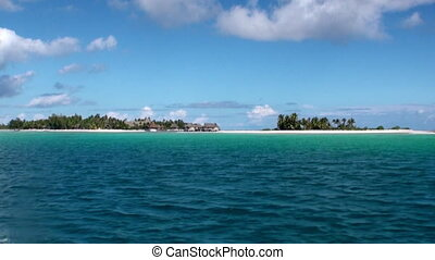 View from a moving boat on hut in ocean. Picturesque wild...