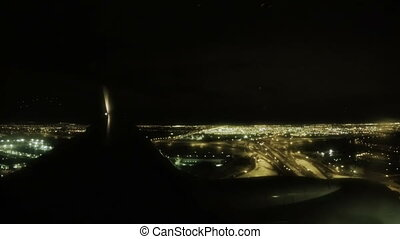 View from a passenger jet window as it lands at night. -...